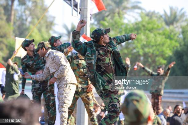 December 2019, Iraq, Baghdad: Iraqi Shiite militia supporters throw stones towards the US embassy in Baghdad during a demonstration against deadly US...