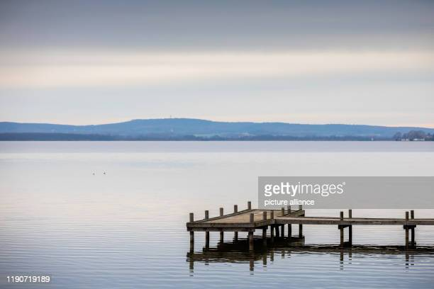 December 2019, Lower Saxony, Wunstorf: A footbridge rises in cloudy weather at the Steinhuder Meer into the calm water. Photo: Moritz Frankenberg/dpa