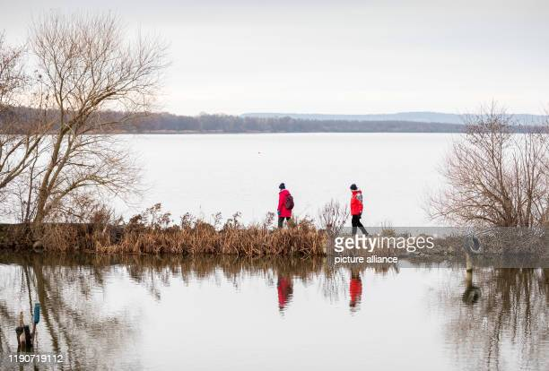 December 2019, Lower Saxony, Wunstorf: Walkers walk along a mole at the Steinhuder Meer in cloudy weather. Photo: Moritz Frankenberg/dpa