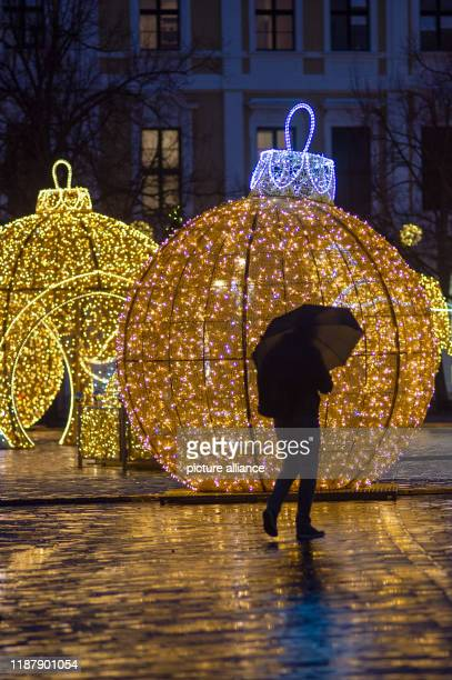 11 December 2019 SaxonyAnhalt Magdeburg A passerby with an umbrella walks across the cathedral square past figures of the world of lights Photo...
