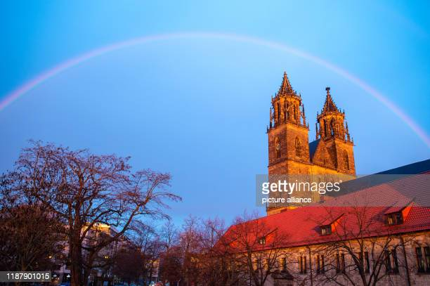 11 December 2019 SaxonyAnhalt Magdeburg A rainbow stands over Magdeburg Cathedral in the early morning The spectacle of nature arose when the rising...