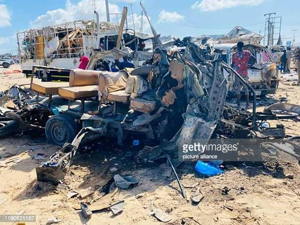 December 2019, Somalia, Mogadishu: The wreckage of a bus stands on the road at a checkpoint after a car bomb attack. At least 18 people were killed...
