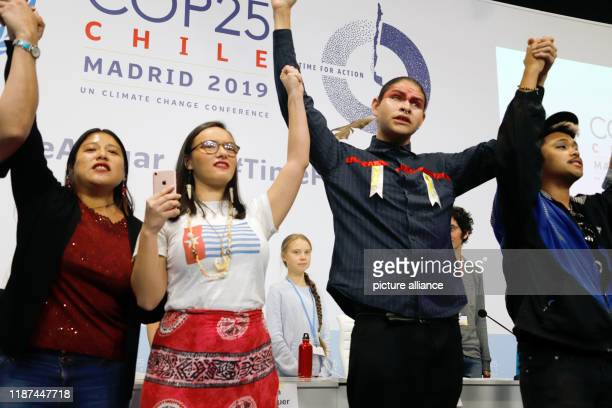 December 2019, Spain, Madrid: Greta Thunberg , Swedish climate activist, stands behind young indigenous climate activists at an event at the UN...