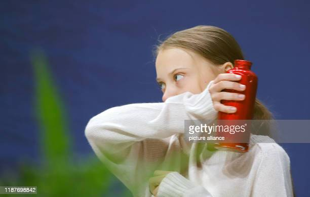 December 2019, Spain, Madrid: Greta Thunberg, Swedish climate activist, sits at an event at the UN Climate Change Conference, holding a red drinking...
