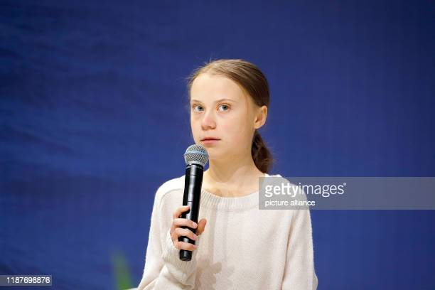 December 2019, Spain, Madrid: Greta Thunberg, Swedish climate activist, speaks at an event at the UN Climate Change Conference, holding a microphone...