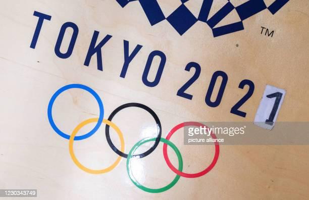 December 2020, Baden-Wuerttemberg, Leinfelden-Echterdingen: The number 0 is covered by a 1 in the 2021 year of a Tokyo Olympics logo in wrestler...
