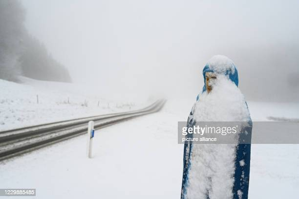 December 2020, Baden-Wuerttemberg, Ravensburg: A figure belonging to a snow-covered field cross stands not far from the community of Hannober. During...