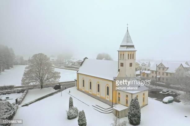 December 2020, Baden-Wuerttemberg, Ravensburg: The catholic church of St. Cassian in Hannober stands snow-covered on the outskirts of the village ....