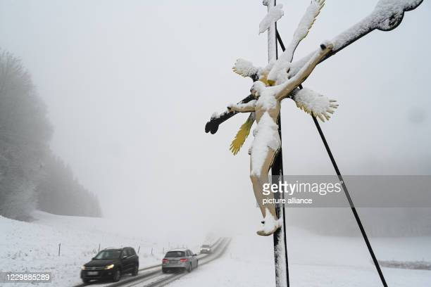 December 2020, Baden-Wuerttemberg, Ravensburg: Three cars drive past a snow-covered field cross. In the night to it has begun to snow. Photo: Felix...