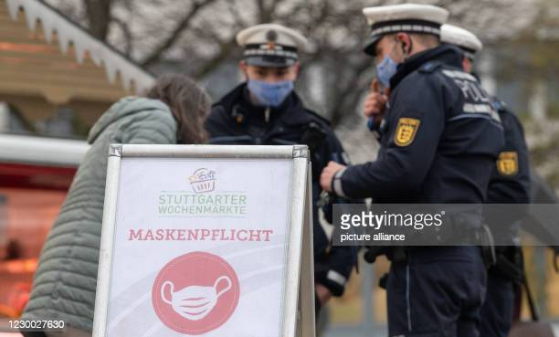 December 2020, Baden-Wuerttemberg, Stuttgart: Police officers inspect a passer-by at a weekly market during a priority inspection for compliance with...