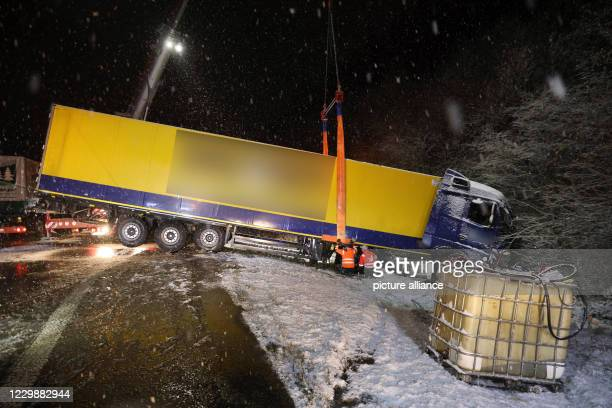 December 2020, Baden-Wuerttemberg, Villingen-Schwenningen: A truck lies in a ditch after a slippery accident on the A81 and is being recovered. The...