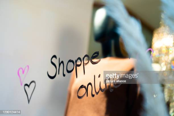 """December 2020, Bavaria, Bamberg: """"Shoppe online"""" is placed on the shop window of a fashion store so that customers can also buy goods online via..."""