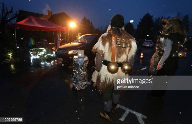 December 2020, Bavaria, Rettenberg: One Santa Claus actor and two Klausen actors are standing at a Santa Claus drive-in in front of a car. So that...