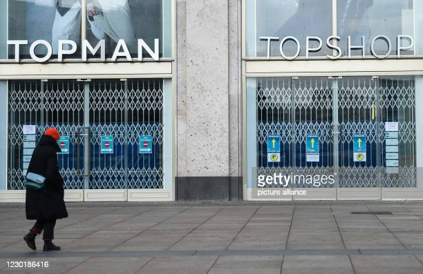 "December 2020, Berlin: A person walks in front of the closed shop ""Topman"" and ""Topshop"". Since , shops must also close due to the imposed lockdown...."