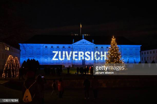 December 2020, Berlin: Federal President Steinmeier and his wife watch as numerous images and messages are projected onto the façade of Bellevue...