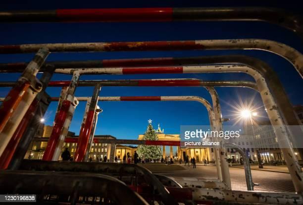 December 2020, Berlin: Police barriers stand in the twilight on Pariser Platz in front of the Brandenburg Gate. Photo: Peter Kneffel/dpa