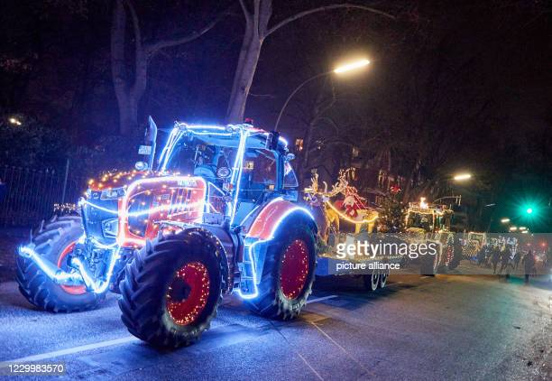 December 2020, Hamburg: A parade of tractors illuminated for Christmas is standing in front of the Children's University Hospital Eppendorf . Farmers...