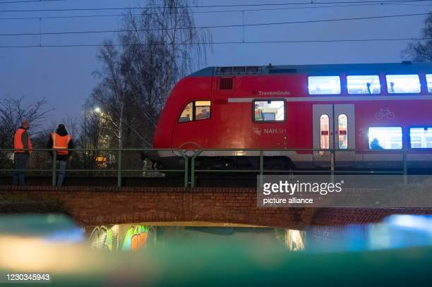 December 2020, Hamburg: Employees of Deutsche Bahn and the Federal Police are standing in front of and inside the regional express train, which has...