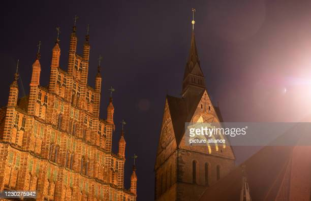 December 2020, Lower Saxony, Hanover: A star is projected onto the tower of the Marktkirche next to the facade of the Old Town Hall . The light...