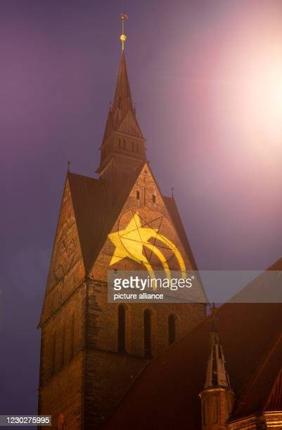 December 2020, Lower Saxony, Hanover: A star is projected onto the tower of the Marktkirche. The light artwork is intended to give people hope and...