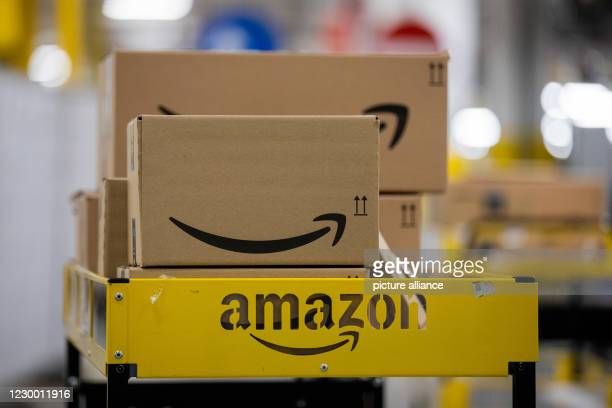 December 2020, North Rhine-Westphalia, Mönchengladbach: Parcels are placed on a trolley in a logistics centre of the mail order company Amazon. A...