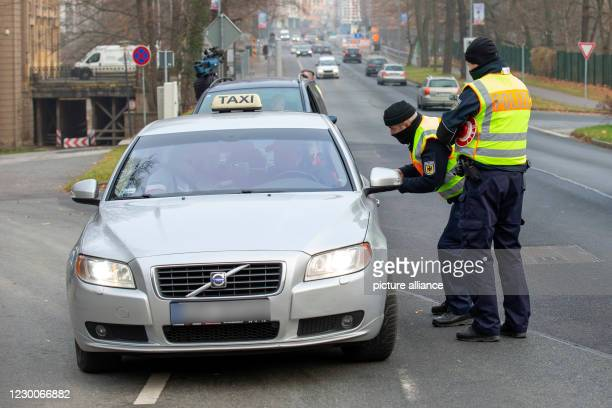 December 2020, Saxony, Görlitz: Two policemen of the Federal Police control a taxi on the city bridge, which has entered Germany from Poland. Police...