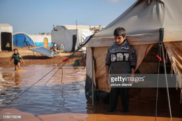 December 2020, Syria, Kafr Aruq: A Syrian boy stands amidst the muddy water outside his tent that has been flooded as a result of heavy rain at a...