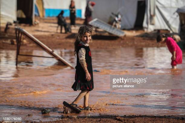 December 2020, Syria, Kafr Aruq: A Syrian girl wades through the muddy water in front of tents that have been flooded as a result of heavy rain at a...
