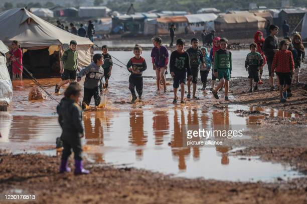 December 2020, Syria, Kafr Aruq: Syrian children play amidst the muddy water after their tents have been flooded as a result of heavy rain at a...