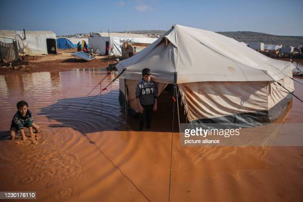 December 2020, Syria, Kafr Aruq: Two Syrian boys stand amidst the muddy water outside their tent that has been flooded as a result of heavy rain at a...