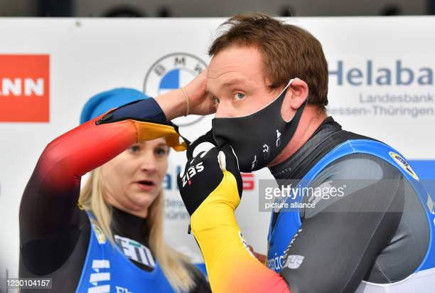 December 2020, Thuringia, Oberhof: Felix Loch and Dajana Eitberger from Germany help each other to put on the masks at the finish line at the...
