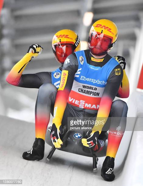 December 2020, Thuringia, Oberhof: Toni Eggert and Sascha Benecken from Germany in the men's double-seater will cheer at the finish of the Luge World...