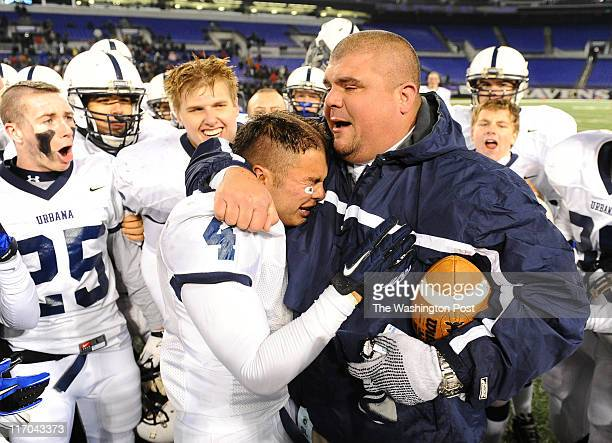 Urbana Head Coach Ryan Hines with tears rolling down his cheeks hugs RB/LB Blake Gatewood following their 60 win over Wise on December 3 2010 in...