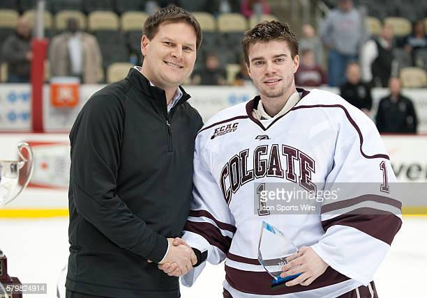 Colgate Raiders goaltender Charlie Finn is handed the Tournament MVP Award by Pittsburgh Penguins Assistant General Manager Jason Botterill after...