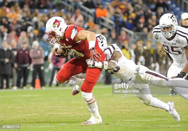 Louisville Cardinals tight end Cole Hikutini drags Texas AM Aggies defensive back Armani Watts during an college football game between the Louisville...