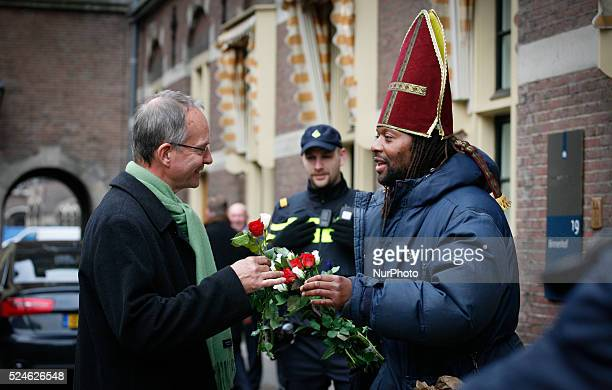 December 5 2014 in The Hague Netherlands Henk Kamp minister of economic affairs receives a rose from a man trying to srpead a positive message about...