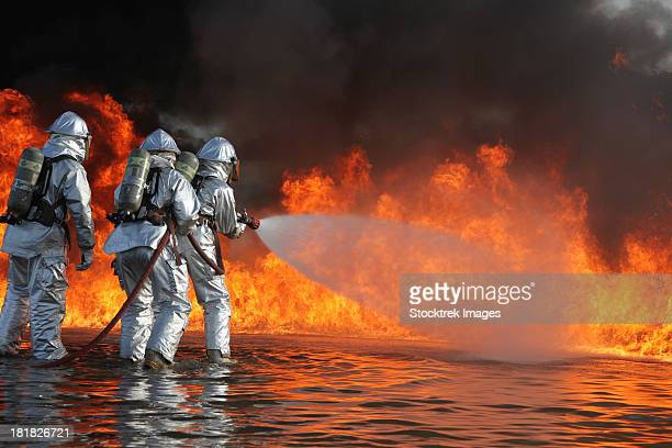 december 7, 2011 - aircraft rescue and firefighting marines battle a huge blaze during a pit fuel fires training exercise at the burn pit. - fire protection suit - fotografias e filmes do acervo