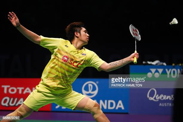 Dechapol Puavaranukroh of Thailand hits a return during the men's doubles Sudirman Cup match with partner Bodin Issara against Seung Jae Seo and Choi...
