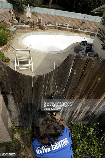 Dechenne Cecil a vector control technician with San Bernardino County collects mosquitoes from an insect trap near an empty swimming pool where...