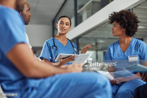 deciding on a course of treatment for their patients - group of doctors stock pictures, royalty-free photos & images