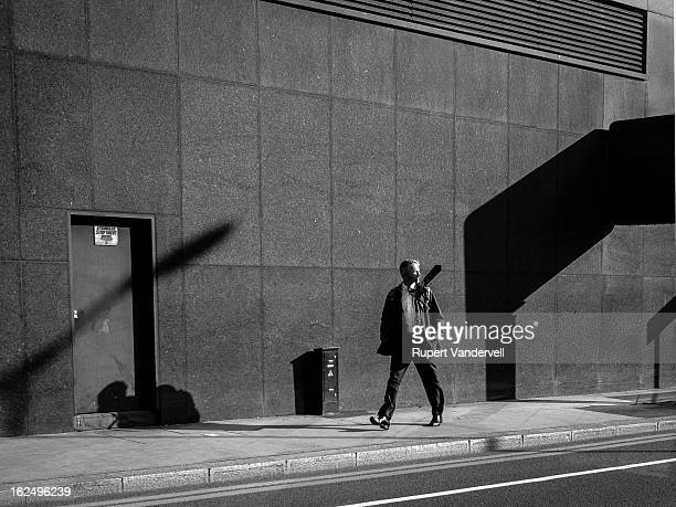 Decisive moment and slightly surreal image of a man walking distractedly down a sunlit street whose walls contain dark geometrical shadows that all...