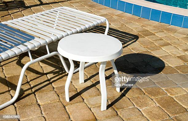Deck chair and a backless chair by the pool