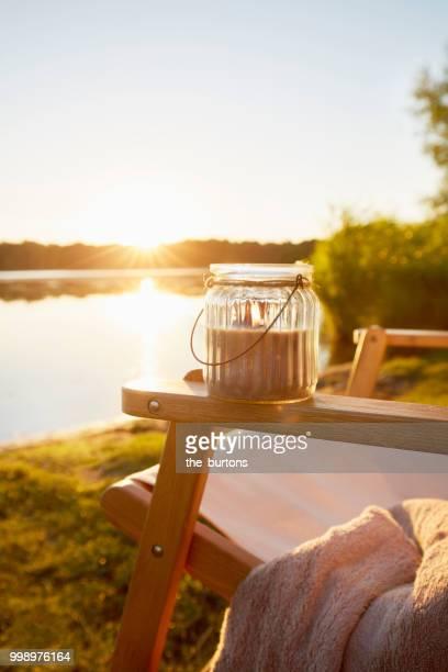 deck chair and lantern at lakeside at sunset - form ändern stock-fotos und bilder