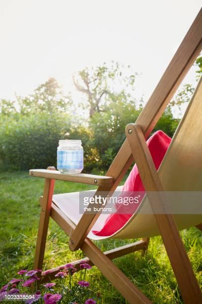 deck chair and pillow in garden - chaise longue photos et images de collection