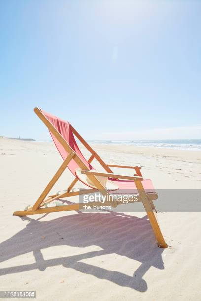 deck chair on beach against blue sky - straw hat stock pictures, royalty-free photos & images