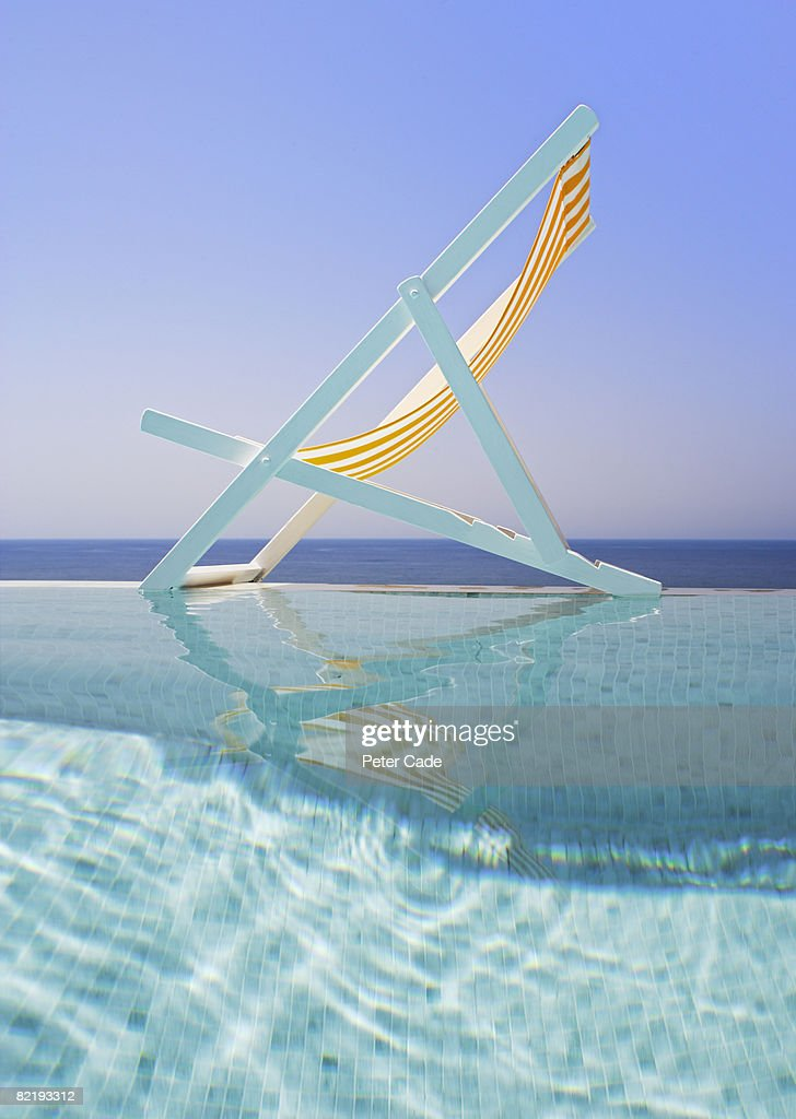 Deck chair on edge of pool : Stock Photo