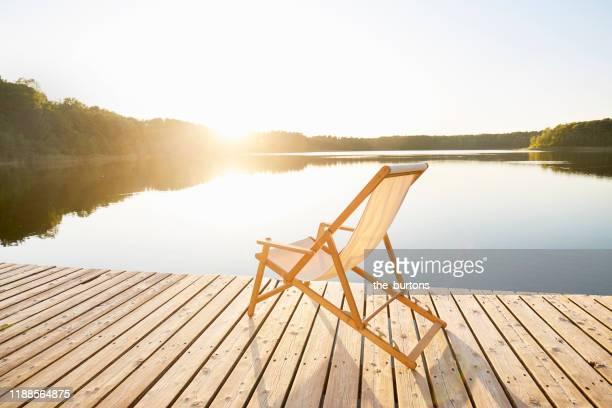 deck chair on jetty at an idyllic lake during sunset - bootssteg stock-fotos und bilder