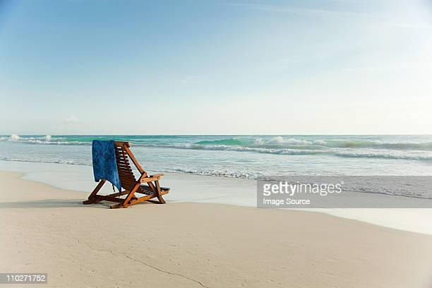 deck chair on sandy beach at water's edge - outdoor chair stock pictures, royalty-free photos & images
