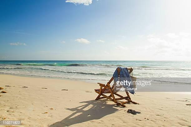 Deck chair on sandy beach at water's edge