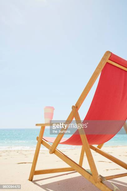 Deck chair with coffee cup on the beach
